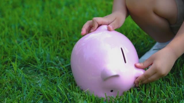 Child shaking piggy bank