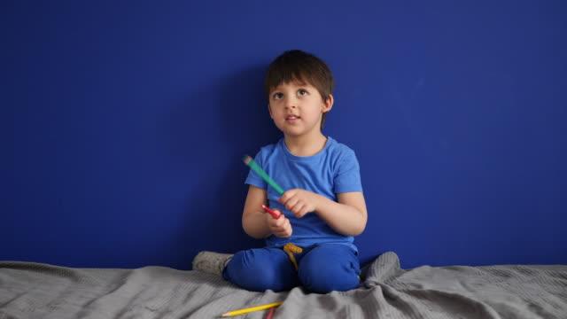 l'enfant s'assied à la maison sur un sofa dans un T-shirt bleu joue à la maison - Vidéo