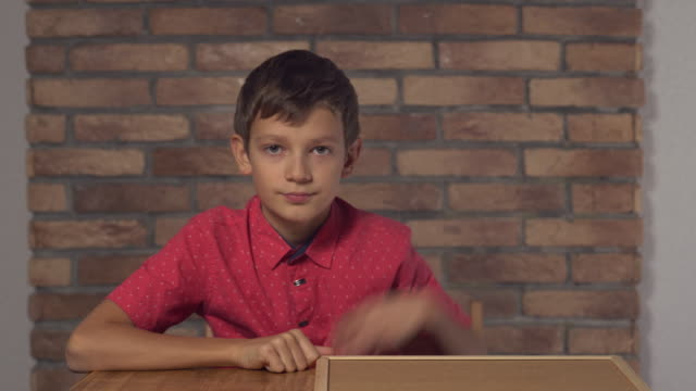 child sitting at the desk holding flipchart with lettering trend on the background red brick wall video
