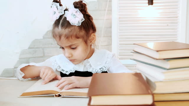 A child sitting at the table leads finger across the page book in the foreground stack of books. video