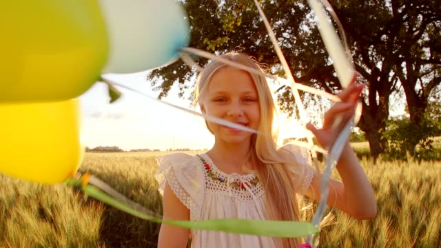 Child spinning with balloons at wheat field . Girl looking at camera. Lens flare and sunlight video