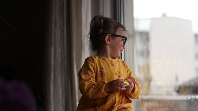 vídeos de stock e filmes b-roll de child standing at window in room and looking delighted - isolated house, exterior