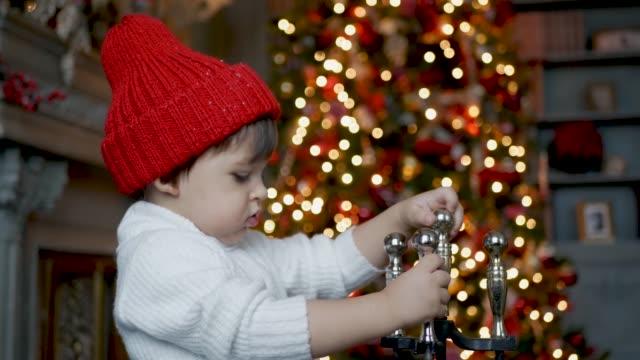 vídeos de stock, filmes e b-roll de a criança está na frente de uma árvore de natal com os brinquedos perto da chaminé - tule têxtil