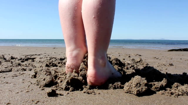 Child Stepping On A Sandcastle On A Sunny Beach Child stepping on a sandcastle on a beach in sunny North Wales in the UK. stamping feet stock videos & royalty-free footage