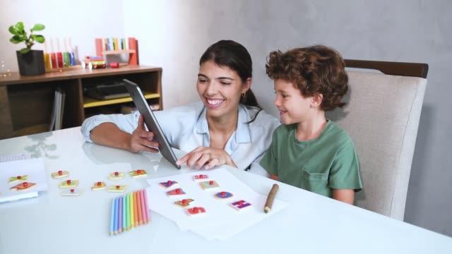 child studying at home with mother during quarantine - один родитель стоковые видео и кадры b-roll