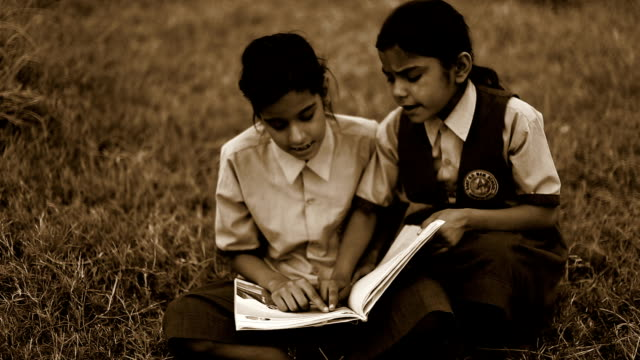 Child studying together outdoor in nature Elementary age teenage girls sitting outdoor in nature on the grass & studying book together wearing school uniform. sepia toned stock videos & royalty-free footage