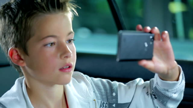 Child take a footage with smartphone on the back seat video
