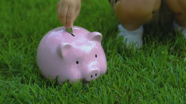 Child throws coins into the piggy bank