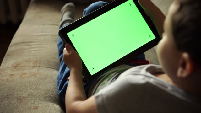 Child tilting to the left and right a tablet PC with green screen, back view video
