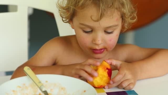 child toddler eating peach fruit - pesche bambino video stock e b–roll