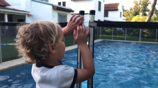 stockvideo's en b-roll-footage met kind probeert te openen zwembad veiligheidshek - fence