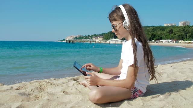 plajda tablette çocuk yazarak. kız müziği dinliyor. - dijital yerli stok videoları ve detay görüntü çekimi