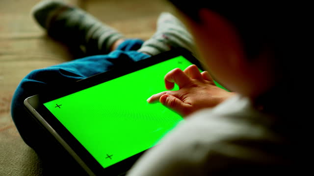 BACK VIEW: Child using a digital tablet PC with green screen at home video