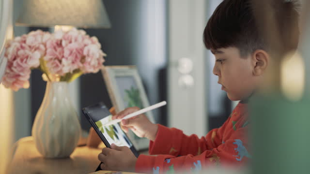 Child using digital pen and tablet. Preschool class, distance learning. child playing with digital tablet at home. Boy using Drawing App On Digital Tablet. video