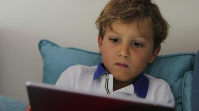tablet teknik cihaz kullanarak çocuk. yeni medya genç çocuk oyun video oyunları 4 k ekran - dijital yerli stok videoları ve detay görüntü çekimi