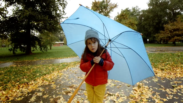 Child walking in the rain with umbrella. video