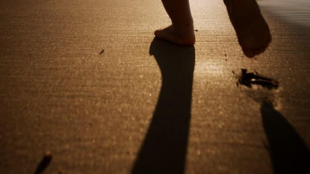 Child walking on beach video