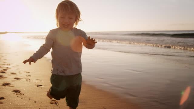 Niño caminando en la playa - vídeo