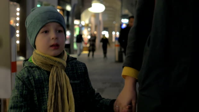 Child walking with mother in evening city street video