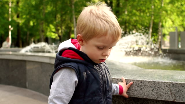 Child walks in Park near the fountain in spring. video