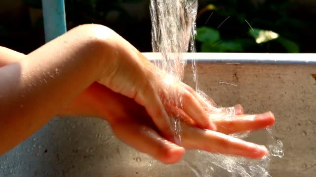 vídeos de stock, filmes e b-roll de criança lavando as mãos com água - lavar as mãos
