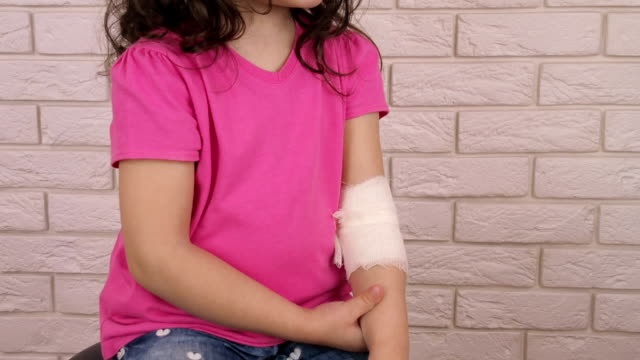 a child with a bandaged hand - rana filmów i materiałów b-roll