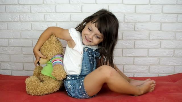 kind mit einem spielzeug-teddy-bären. - rücken an rücken stock-videos und b-roll-filmmaterial