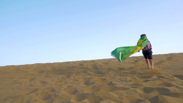 barn med brasilianska flaggan springandes på sanden - brasilien flagga bildbanksvideor och videomaterial från bakom kulisserna