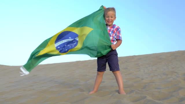barn med brasiliansk flagga stranden - brasilien flagga bildbanksvideor och videomaterial från bakom kulisserna