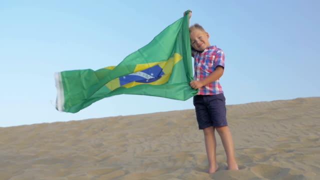 barn med flagga brasilien på stranden - brasilien flagga bildbanksvideor och videomaterial från bakom kulisserna