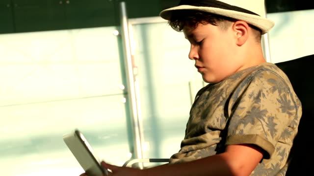 bambino con cappello con i pad - solo un bambino maschio video stock e b–roll