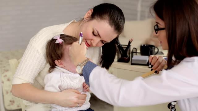 a child with her mother at a doctor's appointment. - szpatułka przybór do gotowania filmów i materiałów b-roll