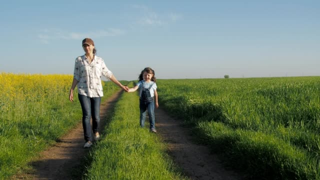 a child with mother in the field. - agricoltrice video stock e b–roll