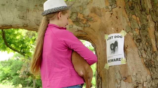 Child with puppy reads lost pet sign on tree trunk