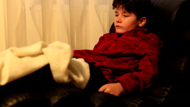 Child with remote controller lying on a sofa and sleeping video