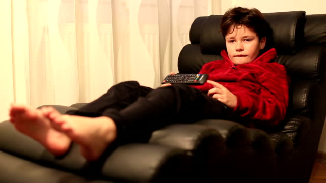 Child with remote controller lying on a sofa video