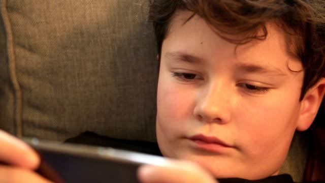 child with smartpnone gaming at home - solo un bambino maschio video stock e b–roll