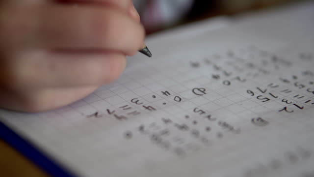 Child working on math homework using graph paper Child working out multiplication problem in her notebook. mathematics stock videos & royalty-free footage