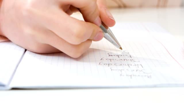 child writing homework close-up - çalışma kitabı stok videoları ve detay görüntü çekimi