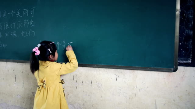 Child writing in Chinese on the blackboard video