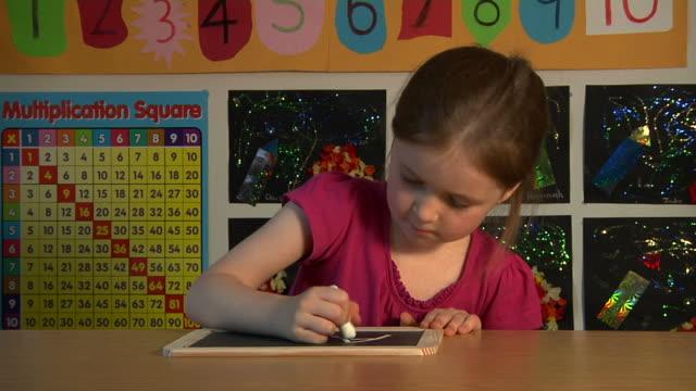 Child writing on chalk board video