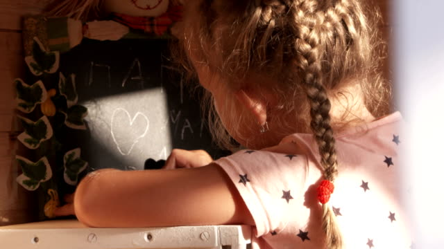 Child writing phrase in Russian on the blackboard I love Mom and Dad video