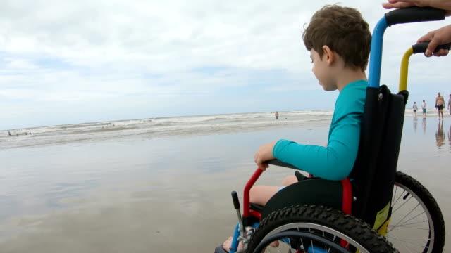 vídeos y material grabado en eventos de stock de arena de horizonte de silla de ruedas infantil - wheelchair