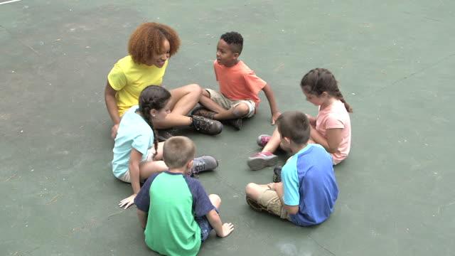 Niños y consejero de campamento suben y se sientan en círculo - vídeo