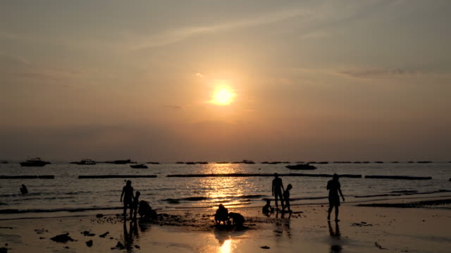 Children and family playing with sand on beach at Pattaya, silhouette - Footage Video