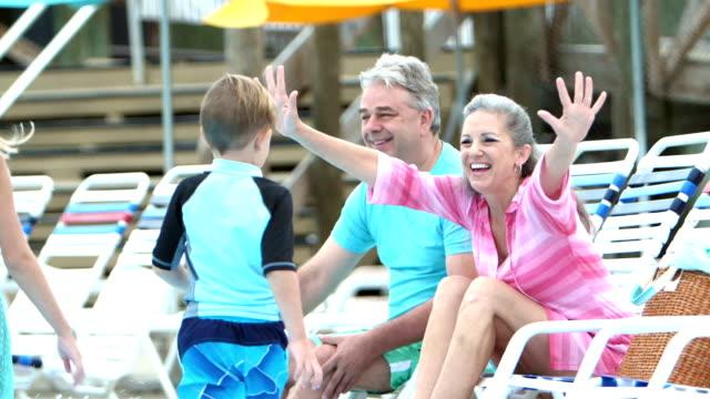 Children and grandparents hugging poolside video