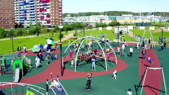 children and parents play on playground in park aerial view