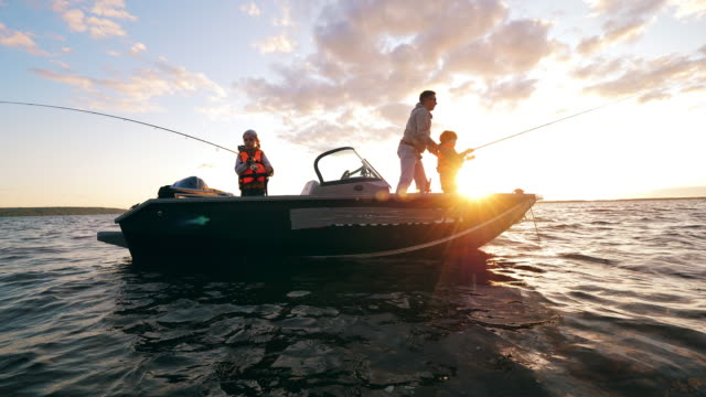Children are fishing from a boat with their dad
