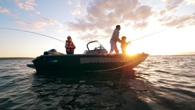 vídeos de stock, filmes e b-roll de crianças estão pescando de um barco com seu pai - veículo aquático