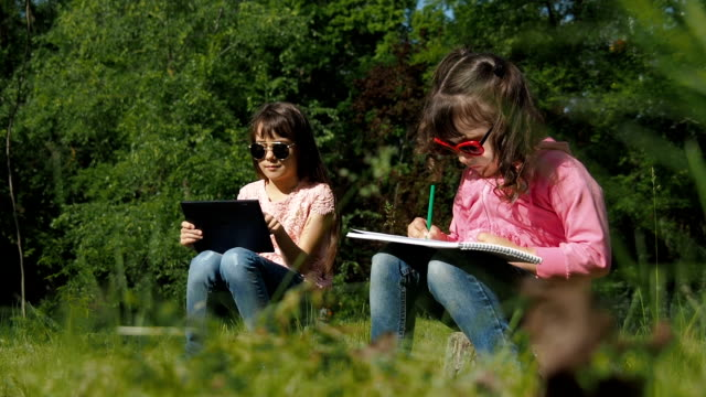 Children are painting in nature. Sisters in the park.